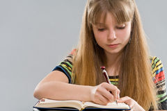 Teenager girl writing down to notepad Stock Images