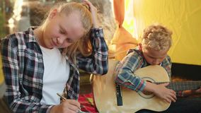 Teenager girl writing song to guitar music in camping tent. Boy teenager playing music on acoustic guitar in tourist. Tent. Brother and sister spending leisure stock footage