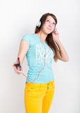 Teenager girl in yellow pants, listening to music from your smartphone Royalty Free Stock Photography