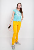 Teenager girl in yellow pants, listening to music from your smartphone Royalty Free Stock Photos