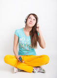Teenager girl in yellow pants, listening to music from your smartphone Royalty Free Stock Images