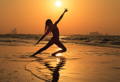 Teenager girl at yoga workout. Teenager girl doing yoga on the beach at sunset time royalty free stock photography