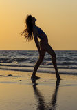 Teenager girl at yoga workout. Teenager gymnast girl doing yoga on the beach at sunset time royalty free stock photos