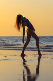 Teenager girl at yoga workout. Teenager gymnast girl doing yoga on the beach at sunset time Royalty Free Stock Image