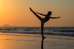 Teenager girl at yoga workout at orange sunset. Teenager gymnast girl doing yoga on the beach at sunset time Royalty Free Stock Photos