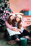 Teenager girls with christmas tree and presents Stock Image