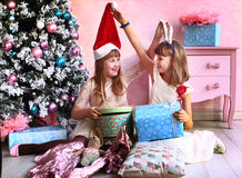 Teenager girls with christmas tree and presents Stock Photos
