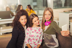Teenager girls hanging out together in a coffee shop Royalty Free Stock Images