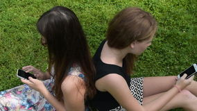 Teenager girls with mobile phones in the park stock video footage