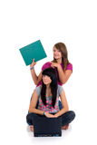 Teenager girls studying. With computer and books on white background Royalty Free Stock Photography