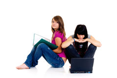 Teenager girls studying. With computer and books on white background Royalty Free Stock Photo