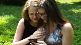Teenager girls using mobile outdoor. Two teenager friends using smart phone outdoor. Girls laughing and arguing about the cell stock footage