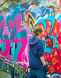 Teenager graffiti painter. LISBON, PORTUGAL - DECEMBER 23, 2014: Teenager painting graffiti on the wall in Lisbon.Along with London, Berlin, New York and others Royalty Free Stock Photos