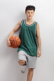 Teenager in green jersey holding basketball and leaning on wall Royalty Free Stock Photography