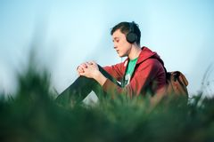 Teenager on green lawn listening music. In headphones. Happy dreamer Royalty Free Stock Image