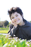 Teenager on the green in the park. Smilling boy  on the green grass Stock Photo