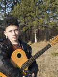 The teenager with guitar. On background wood Stock Image