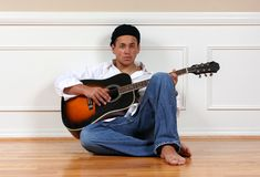 Teenager with guitar. A teenage boy, sitting on the floor with his guitar royalty free stock photo