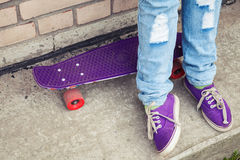 Teenager in gumshoes stands with skateboard stock photo
