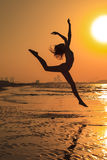 Teenager gymnast girl in active workout. Teenager gymnast girl doing - workout on the beach at sunset time. Girl enjoying active workout royalty free stock photography