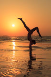 Teenager gymnast girl. Doing - workout on the beach at sunset time. Girl enjoying active workout Stock Photos