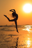 Teenager gymnast girl. Doing - workout on the beach at sunset time. Girl enjoying active workout Stock Image
