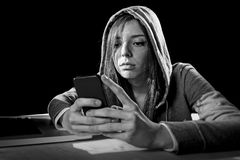 Teenager hacker girl in hood using mobile phone in internet cyber crime expert or cybercrime. Young dangerous looking teenager hacker girl using mobile phone and royalty free stock image
