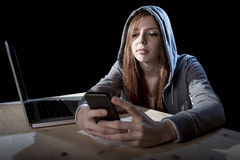 Teenager hacker girl in hood using mobile phone in internet cyber crime expert or cybercrime Royalty Free Stock Photos