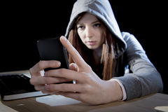 Teenager hacker girl in hood using mobile phone in internet cyber crime expert or cybercrime Royalty Free Stock Images