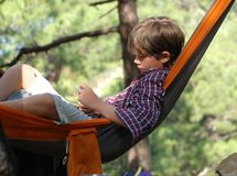 Teenager in a hammock. Crimea trekking. Relax in a hammock. Teenager reading an e-book Stock Photography