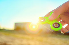 Teenager hand holding  trendy antistress gadget fidget spinner. Man playing with green spinner outdoors on the bright bokeh sunlight rays. Shallow DOF Stock Image