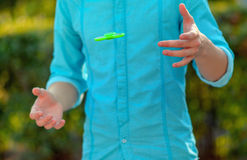 Teenager hand throws  antistress popular gadget fidget spinner. Man on the azure shirt and blue jeans playing with green spinner outdoors  on the bright floral Royalty Free Stock Photography