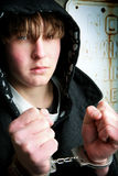 Teenager in handcuffs. Closeup against a wall stock photography