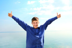 Teenager with hands up. Happy young man spread hands with thumbs up on the seaside background in the sunny day Stock Images