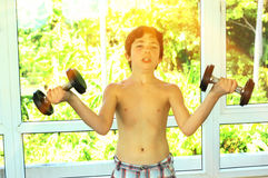 Teenager handsome boy with dumb bells in gym. Exercise hands close up photo Royalty Free Stock Photography