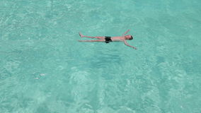 Teenager has a rest on turquoise transparent water of ocean Stock Images