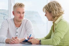 Teenager having a  therapy session. While therapist is taking notes Stock Photography