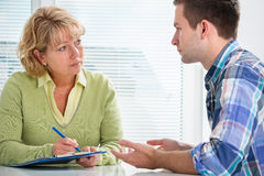 Teenager having a therapy session. While therapist is taking notes Royalty Free Stock Image