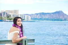 Teenager hawaiano con i leu che si siedono dall'oceano, Waikiki nel fondo Immagine Stock