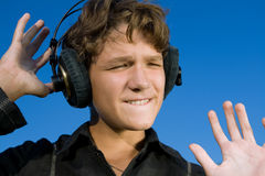 Teenager in headphones. On blue sky background. Close-up Royalty Free Stock Images
