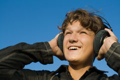 Teenager in headphones. On blue sky background. Close-up Royalty Free Stock Image