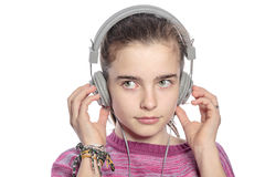 Teenager with headphones hearing music. Female teenager with headphones hearing music, isolated on white Stock Images