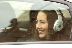 Teenager with headphones listening to the music in a car Royalty Free Stock Photos