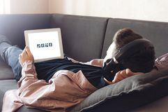 Teenager in headphones listening to music. Lying on the bed Stock Photos