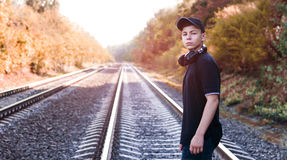 Teenager with headphones listens to music on the railway tracks. Modern young man with headphones listening to music on the railway tracks Royalty Free Stock Photo