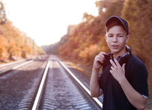 Teenager with headphones listens to music on the railway tracks Stock Photos