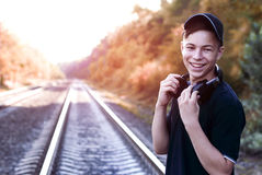 Teenager with headphones listens to music on the railway tracks. Modern young man with headphones listening to music on the railway tracks Stock Photo