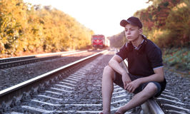 Teenager with headphones listens to music on the railway tracks Royalty Free Stock Photography