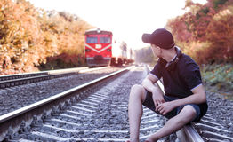 Teenager with headphones listens to music on the railway tracks Stock Images