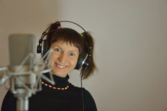 Teenager in the headphones near a microphone in a. The girl in earphones and microphone Stock Photos